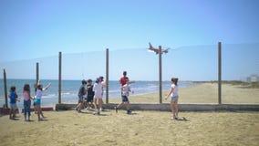 Дети смотрят плоское летание низкое над пляжем акции видеоматериалы