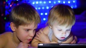 Дети смотрят плиту лежа на кровати На заднем плане, света и ель рождества гирлянды видеоматериал