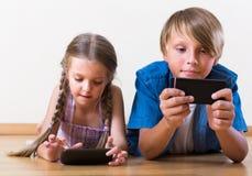 Дети смотря экран smartphones Стоковые Изображения