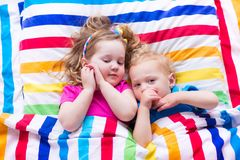 Дети спать под красочным одеялом Стоковое Изображение