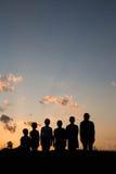 Дети стоят на поле с предпосылкой захода солнца Стоковая Фотография RF