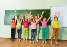 Дети стоят с оружиями вверх в линии около классн классного Стоковая Фотография RF