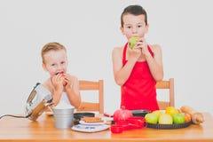 Дети счастливой семьи смешные подготавливают яблочный пирог, на белой предпосылке Стоковое Изображение RF