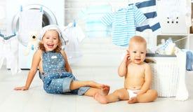 Дети счастливые сестра и брат маленьких хелперов смешные в прачечной к Стоковая Фотография RF