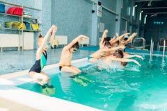Дети с изумлёнными взглядами и флипперами сидят около бассейна стоковое фото rf