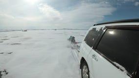 Дети с их отцом едут на пластичной лед-шлюпке связанной к автомобилю Это весьма, опасно и противозаконно Они потеха акции видеоматериалы