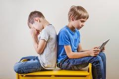 Дети с компьютером Один мальчик используя таблетку и другой ребенк тереть утомлянные глаза после долгого времени играя игру Стоковое Изображение