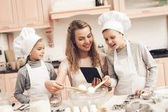 Дети с матерью в кухне Семья читает рецепт на таблетке стоковые изображения