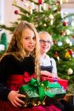 Дети с настоящими моментами и дерево на Рожденственской ночи Стоковое Изображение