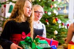 Дети с настоящими моментами и дерево на Рожденственской ночи Стоковое Фото