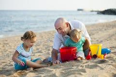 Дети с папой на пляже Стоковые Изображения