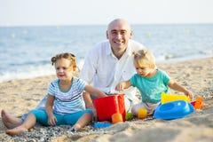 Дети с папой на пляже Стоковые Фото