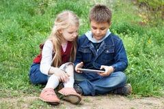 Дети с ПК таблетки outdoors Стоковое Изображение