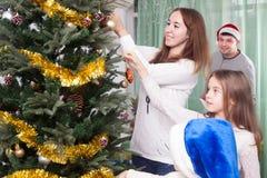 Дети с родителями украшают рождественскую елку Стоковое фото RF