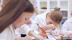 Дети с ручкой печатания 3D изучают современную технологию