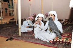 Дети с соколом в звероловстве Абу-Даби международном и конноспортивной выставке 2013 Стоковая Фотография
