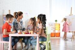 Дети с учительницей на крася уроке стоковая фотография
