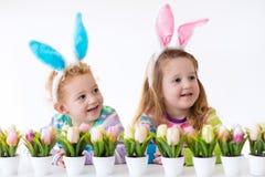 Дети с ушами зайчика на пасхальном яйце охотятся Стоковые Фотографии RF