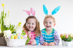 Дети с ушами зайчика на пасхальном яйце охотятся Стоковое Фото