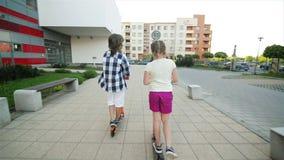 Дети учат ехать самокат на солнечный летний день Игра детей outdoors с самокатами Активный отдых и внешний спорт видеоматериал