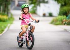 Дети уча управлять велосипедом на подъездной дороге снаружи Стоковая Фотография