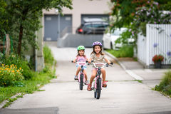 Дети уча управлять велосипедом на подъездной дороге снаружи Стоковое фото RF