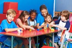 Дети учитель играя с строительными блоками стоковое фото