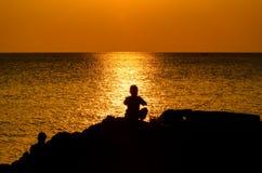 Дети удя силуэт в заходе солнца Стоковые Фотографии RF