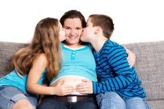 Дети целуя их супоросую мать Стоковые Изображения RF