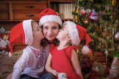 Дети целуя их мать на щеке под рождественской елкой Стоковая Фотография