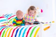 Дети читая книгу в кровати Стоковые Фотографии RF
