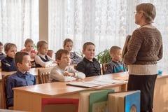 Дети школы в классе с учителем стоковое фото