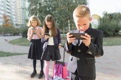 Дети элементарного возраста со смартфонами, рюкзаками, на открытом воздухе предпосылкой стоковое изображение rf