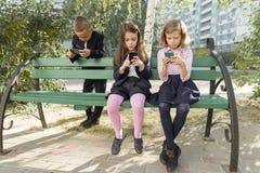 Дети элементарного возраста со смартфонами, рюкзаками, на открытом воздухе предпосылкой стоковая фотография rf