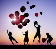 Дети Outdoors играя с воздушными шарами Стоковая Фотография