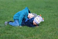 Дети palying, имеющ потеху, лежащ на траве, смеясь над Стоковое фото RF