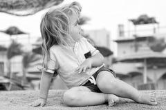 Детская игра на песке Малый мальчик сидит на тропическом пляже Деятельность при лета на пляже Каникулы, отдых и ослабляют концепц стоковая фотография rf
