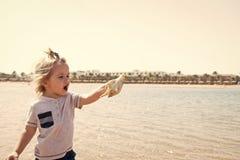 Детская игра с seashell на солнечном seascape Мальчик с раковиной на пляже моря Свобода, открытие и приключение Лето стоковые фото