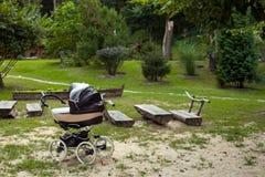 Детская дорожная коляска на луге в парке Стоковые Изображения