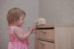 Детские игры с ежом Грызун обнюхивает младенца стоковое изображение