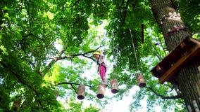 Детский сад малыша Маленькая девочка играя на спортивной площадке Маленькая девочка взбираясь на высоком парке веревочки Маленька сток-видео