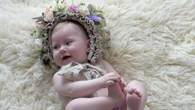 Детство, младенец в обруче с цветками лежит на половике и представляет на камере на photoshoot сток-видео
