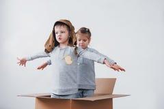 детство шаловливое Мальчик имея потеху с картонной коробкой Мальчик претендуя быть пилотом Мальчик и девушка имея потеху Стоковая Фотография