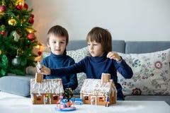 2 дет, братья мальчика, играя с домами пряника Стоковое фото RF