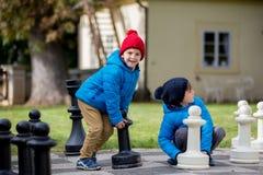 2 дет, братья мальчика, играя шахмат с огромными диаграммами в t Стоковые Изображения