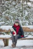 2 дет, братья мальчика, сидя на стенде в парке, winterti Стоковые Изображения RF