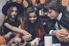 3 дет в костюмах извергов на хеллоуине сидят на поле и украшают череп оленей Стоковое фото RF