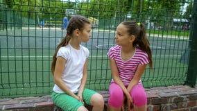 2 дет говоря секреты и смеясь над в парке, outdoors Стоковое фото RF