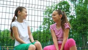 2 дет говоря секреты и смеясь над в парке, outdoors Стоковая Фотография