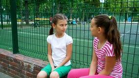 2 дет говоря секреты и смеясь над в парке, outdoors Стоковое Фото